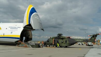 A giant nose-loading plane and a helicopter in front after being removed from the plane.