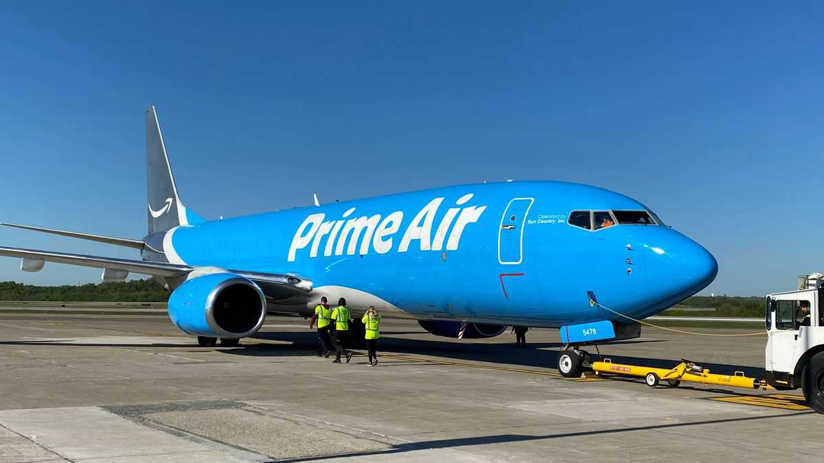 A light blue Amazon Air 737 freighter parked with pusher vehicle.