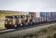 A photograph of a BNSF locomotive hauling intermodal containers across a desert.