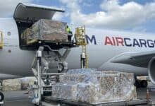 A white airplane with AIR CARGO written on the side gets loaded through side door.