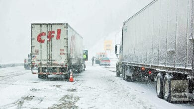 Tractor-trailers stopped on a snow-covered Colorado highway.