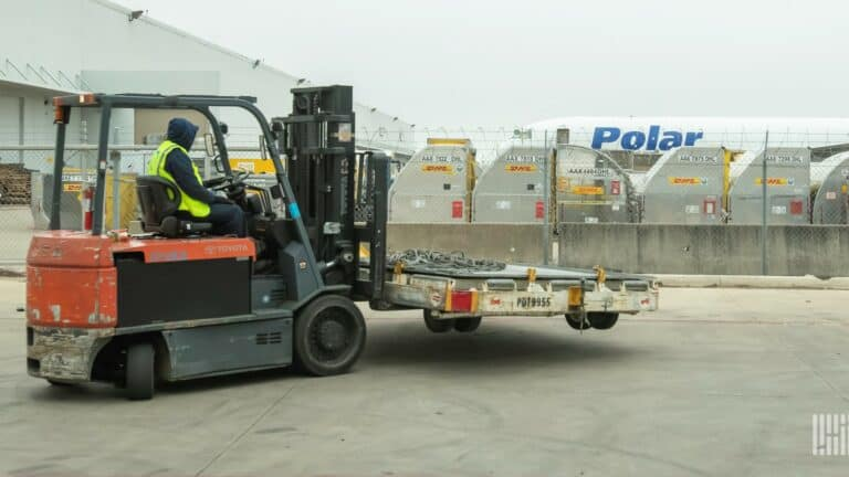 A forklift driver with a pallet, airfreight containers in a row and an aircraft in the background.