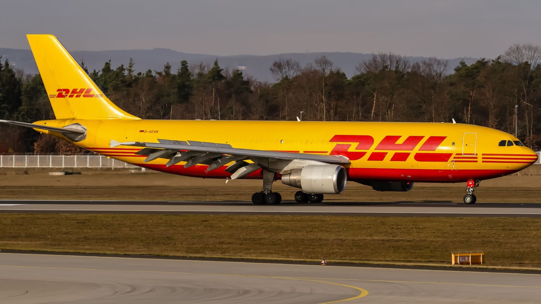 A mustard-colored DHL cargo jet on airport taxiway.