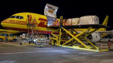 A mustard DHL cargo jet with red lettering loaded with cargo at night.