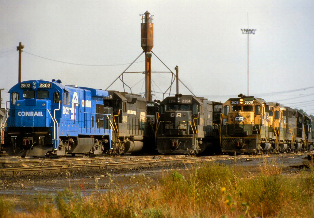 """The early Conrail """"Rainbow Era"""" shows four different Conrail locomotives; only one is painted with Conrail's blue/white color scheme. The railroad inherited a mix of locomotives of vastly different ages built by different companies. A new locomotive sits next to former Penn Central and Reading units at the old New York Central terminal in Elkhart, Indiana in September 1977.  (Photo: American-Rails.com/Rob Kitchen)"""