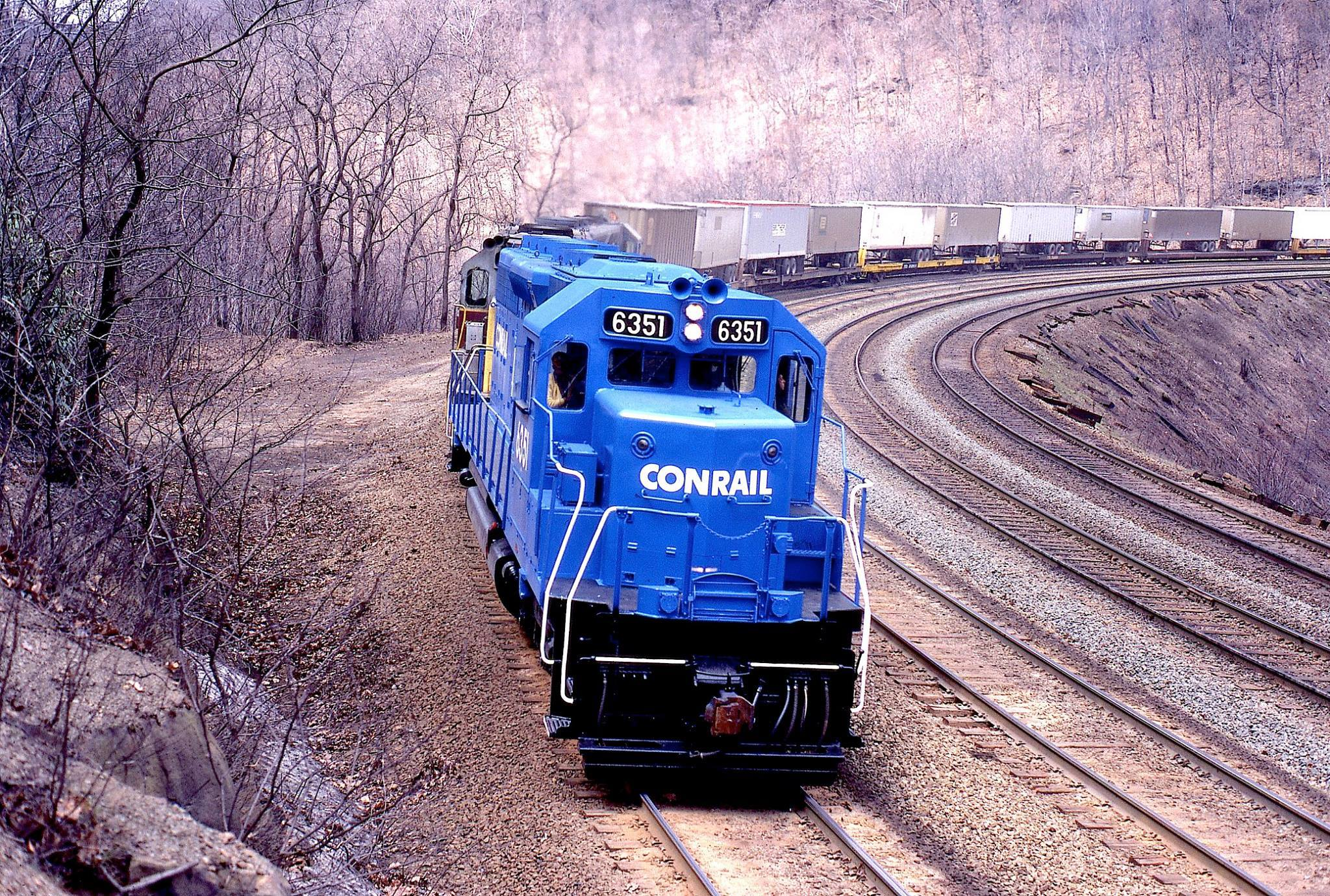 A repainted Conrail locomotive (originally belonging to the Pennsylvania Railroad) grinds upgrade with trailers on flat cars on the famous Horseshoe Curve. Note that when this photo was taken all four tracks were still in service.  (Photo: American-Rails.org/Warren Calloway)