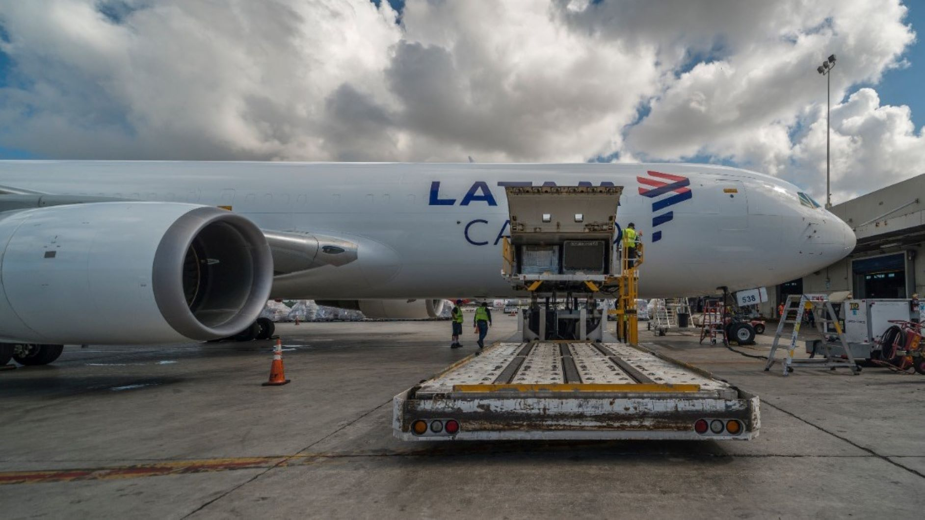 Side view of a white cargo jet with the side door wide open and a dolly in the foreground.
