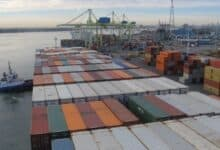 A tugboat helps park a large containership at the Port of Montreal. by pushing it into the wharf.