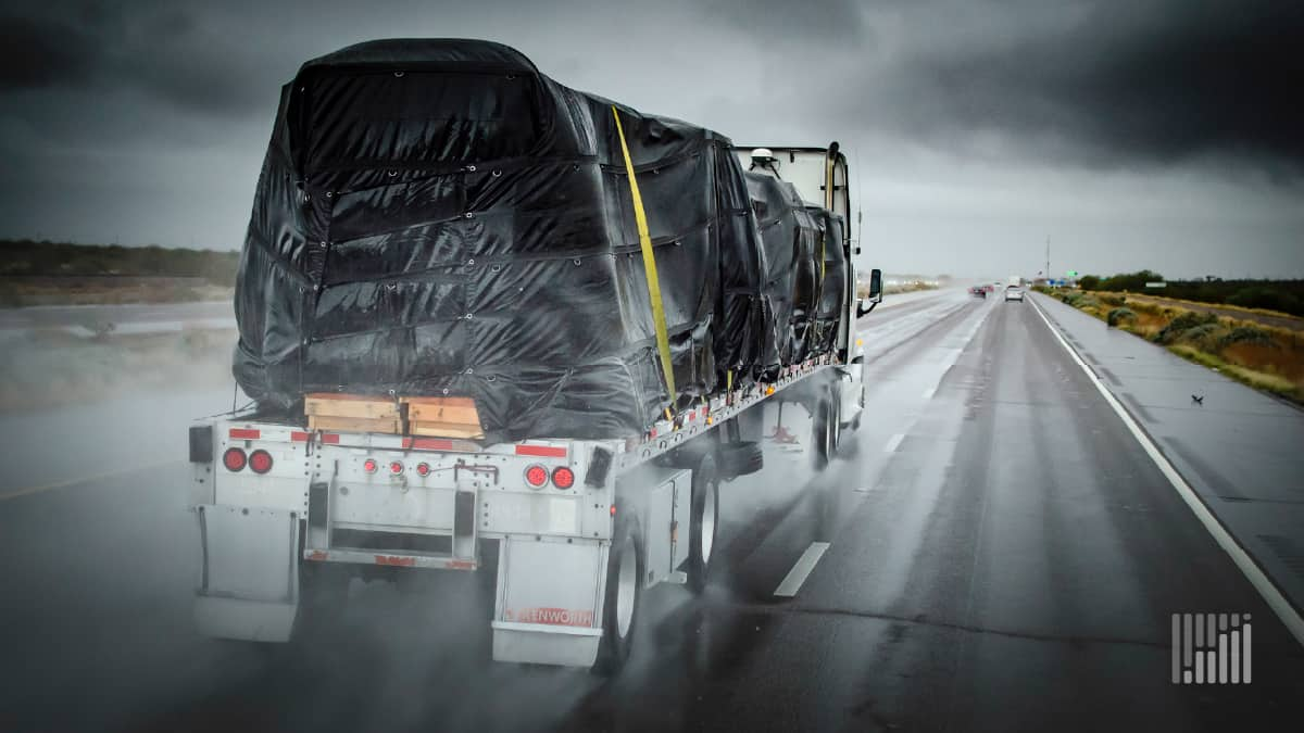 Flatbed tractor-trailer heading down road on a rainy day.