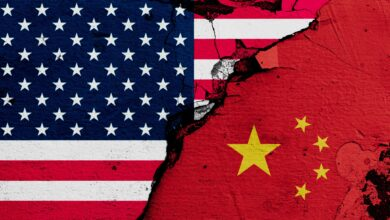 Image of U.S. and Chinese flags, with a rupture between them indicating conflict.