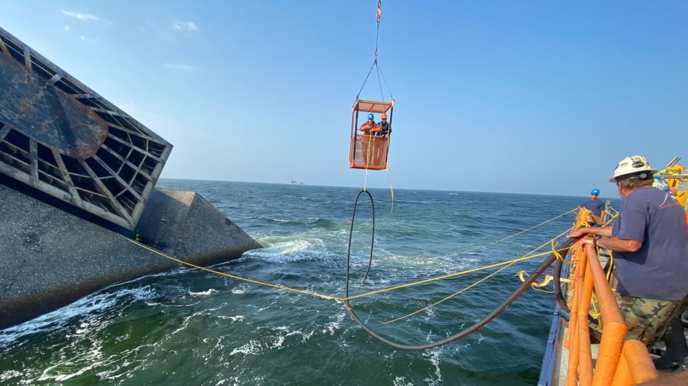 Salvage divers transport a hose to the SEACOR Power fuel tank to start removing the fuel.