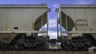 A photograph of hopper cars on a train track.