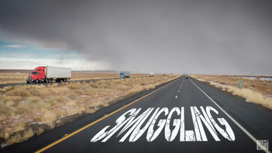 A image of the word 'smuggling' on a highway as truck pass by.