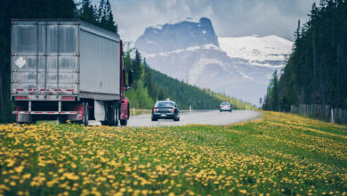 A truck travels on a road with mountains in the background in Alberta, Canada, where a trucking company shut down.