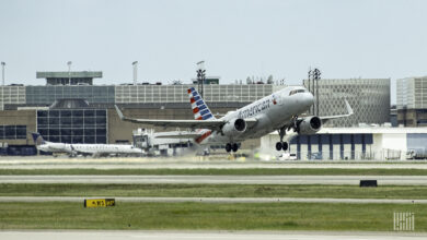 An American Airlines plane takes off with wheels just off the ground.