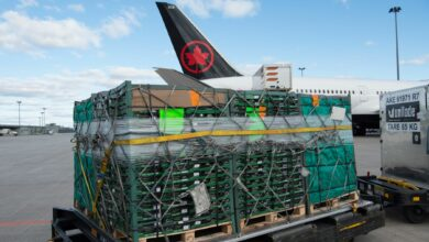Cargo pallets on the tarmac waiting to be loaded on an Air Canada plane.