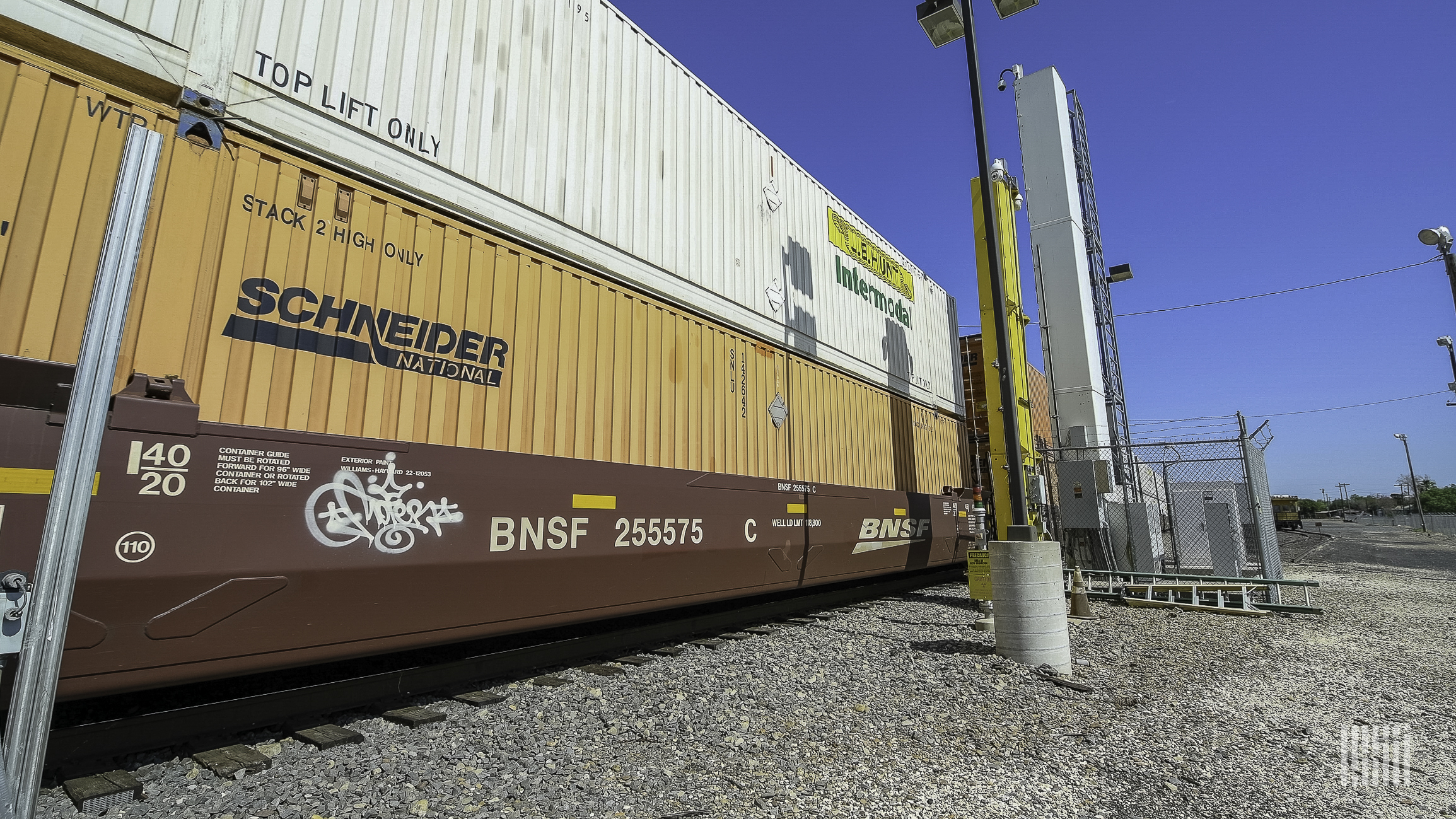 A photograph of intermodal containers stacked on a freight train.