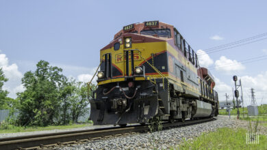 A photograph of a Kansas City Southern locomotive hauling intermodal containers.