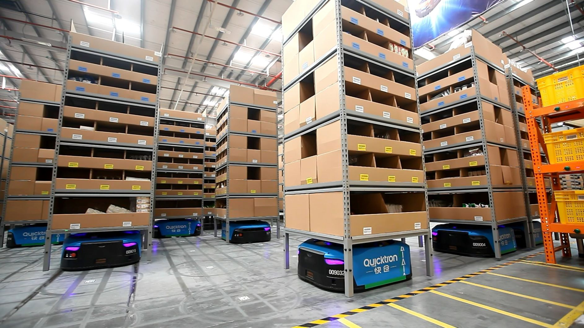 Small robots move bins of goods in an automated warehouse.