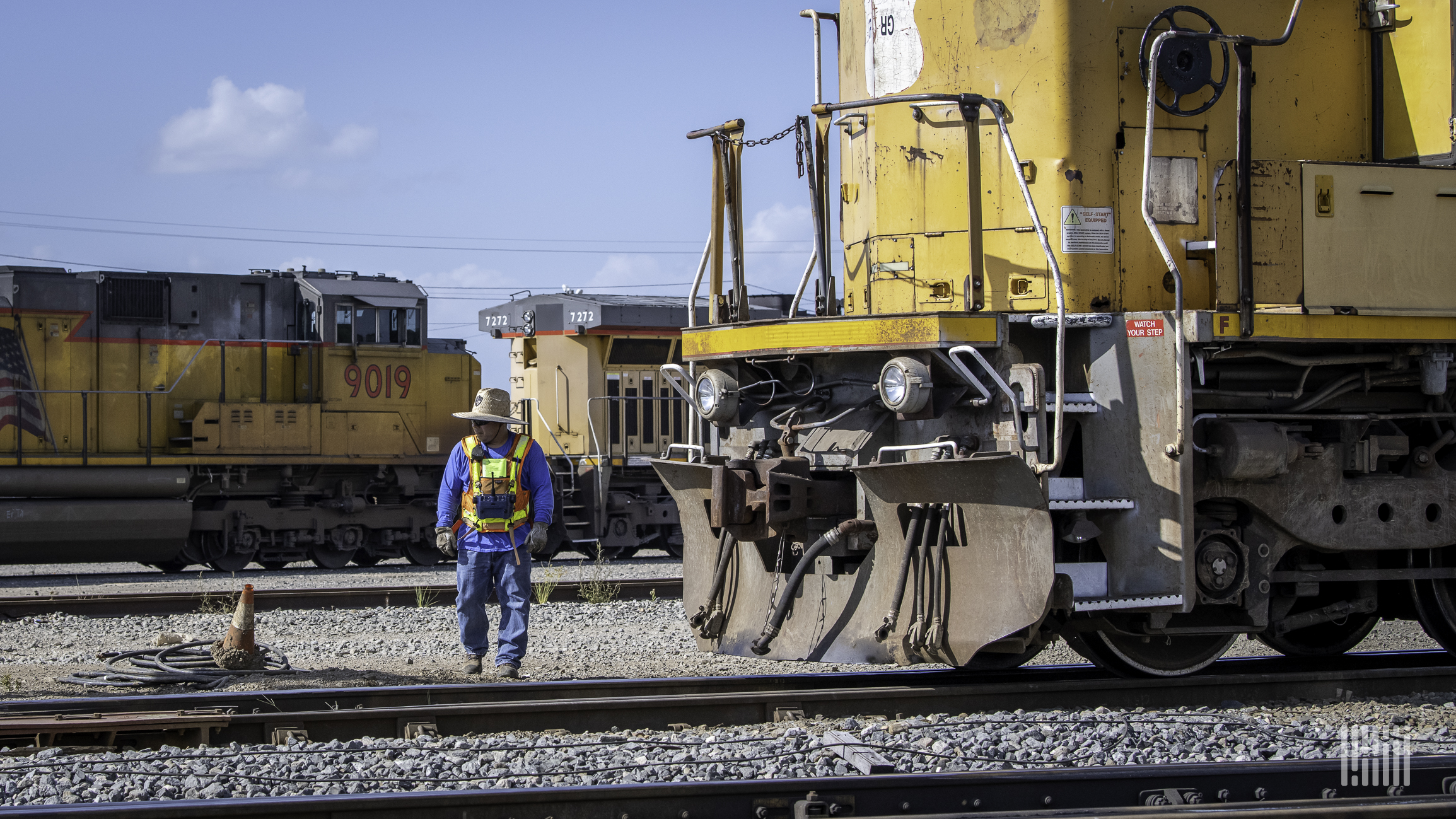 A photograph of a man walking by a locomotive in a rail yard.