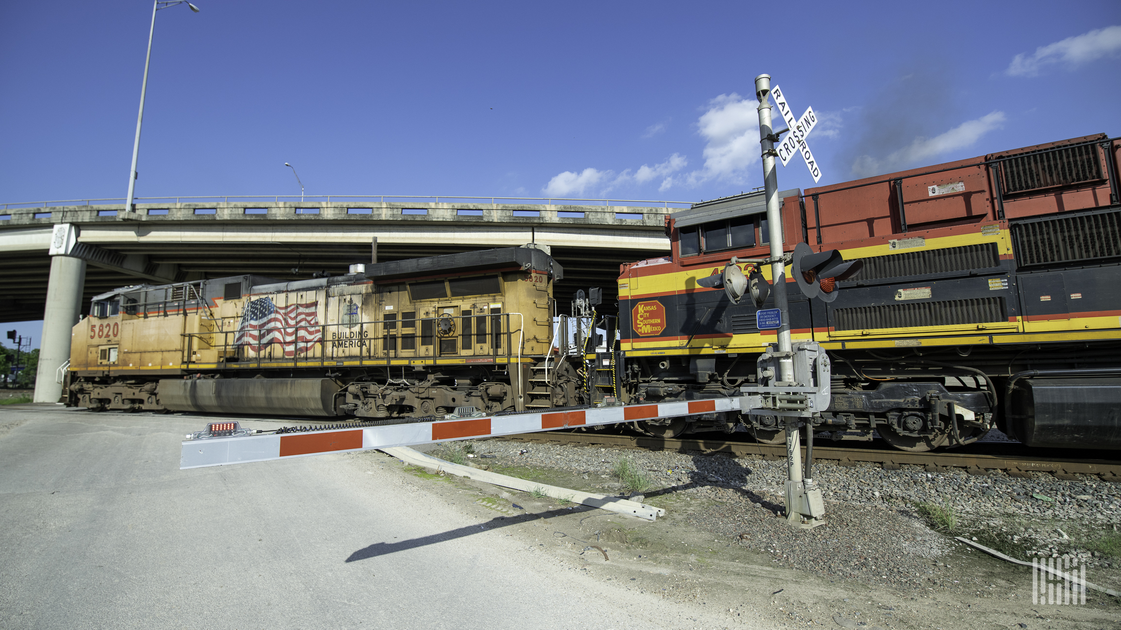 A photograph of a Union Pacific locomotive and a Kansas City Southern locomotive at a rail crossing.