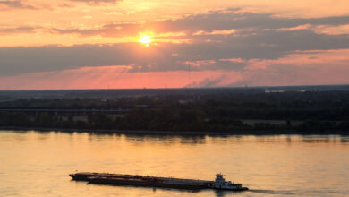 A photograph taken at sunset of a barge sailing down a river.