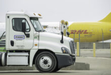 Back half of a mustard-colored DHL plane in background and tractor-trailer cab in foreground at airport.