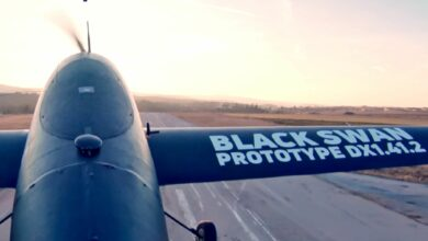 A close up of a winged, cargo drone from top of fuselage looking forward on runway.