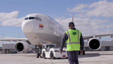An airport worker with a yellow vest walks towards an airplane and a ground tug.
