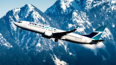 A white WestJet plane axcends with snow-covered mountains as backdrop.
