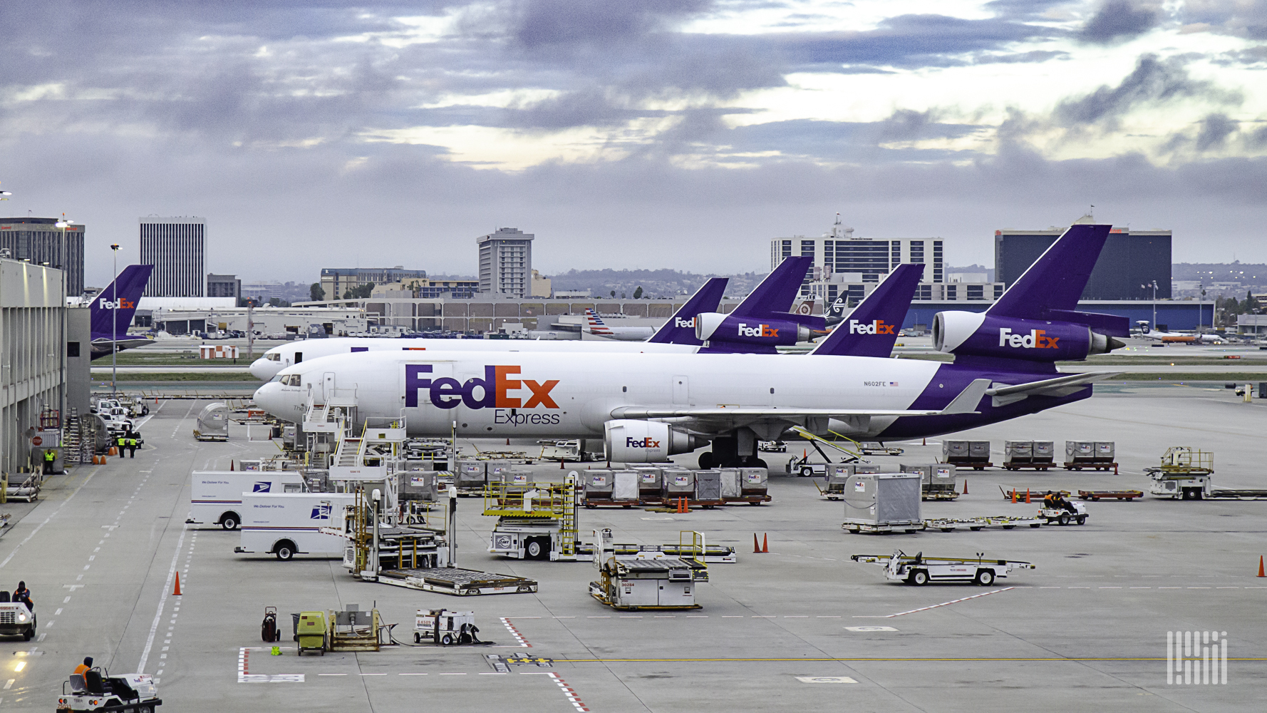 Several FedEx planes lined up at an airport terminal.