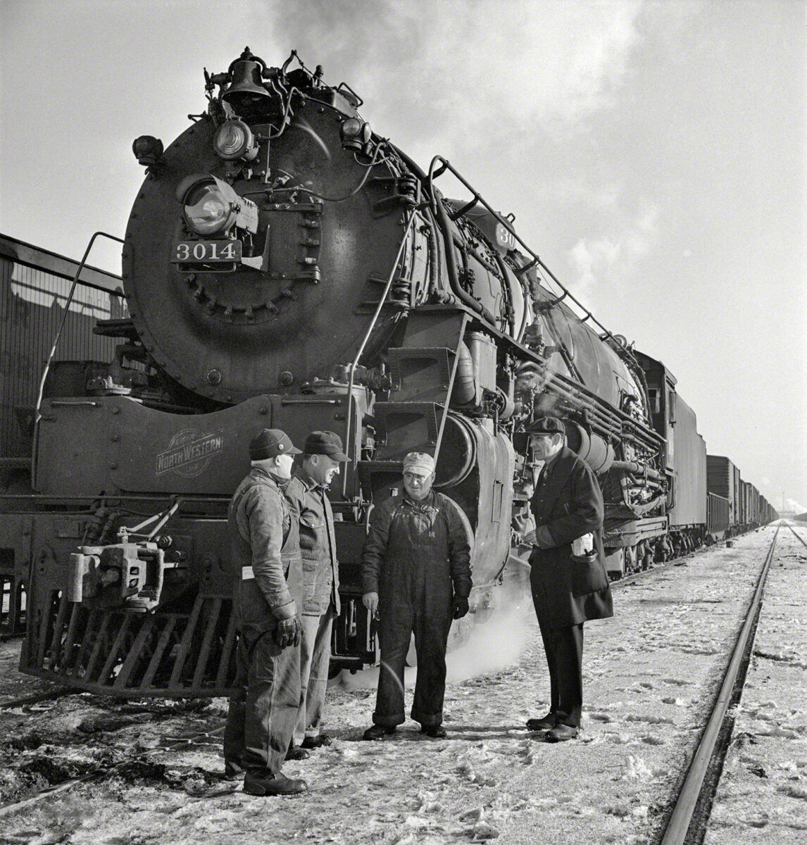 A Chicago & North Western crew, standing beside a 1929 Baldwin locomotive, talk while waiting for orders to pull out during a cold January day in 1943. (Photo: Jack Delano)
