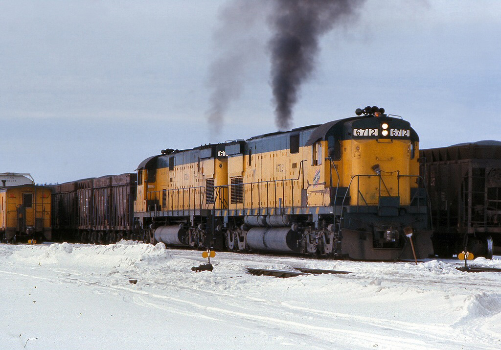 A pair of big C628's throttle up as they work a heavy cut of ore jennies through Euclid Yard in Ishpeming, Michigan in February 1976. (Photo: Rob Kitchen)