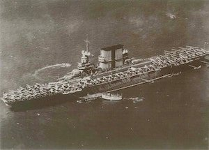 Crowley tugs escort an early aircraft carrier. (Photo Crowley)
