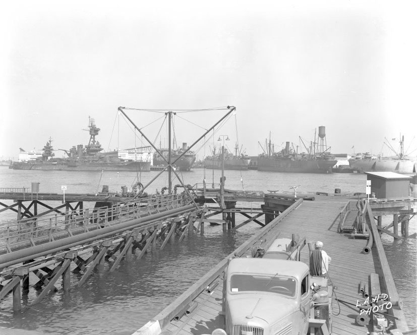A general view looking east from Berth 86, showing the S.S. Maliko (in front of sprinkler tank) docked at Berth 232-E. The battleship U.S.S. New York is docked at Berth 231. The S.S. Maliko carried the first non-priority civilian shipments inbound and outbound from Los Angeles Harbor, after the end of World War II. (Photo: Port of Los Angeles)