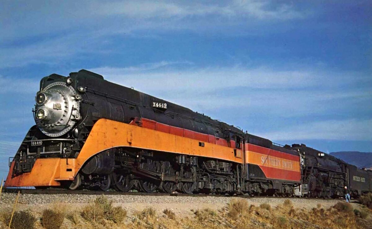 """A pair of Southern Pacific's famous GS-4 """"Golden States,"""" one wearing her iconic """"Daylight"""" livery (famous #4449) and the other in drab black (#4447, which has also lost her modest streamlining), are paused at Humphreys, California with a special fan trip on October 17, 1954. Richard Kindig photo."""