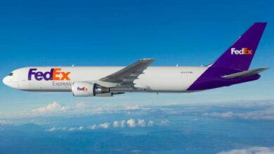 A white FedEx plane with blue tail flying above the clouds.