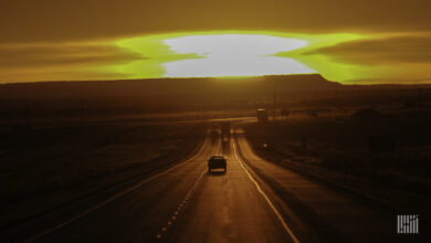 Cars and trucks heading down a highway with hot sun on the horizon.
