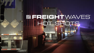 """Line of tractor-trailers on a highway at night with """"FreightWaves Hot Shots"""" logo."""
