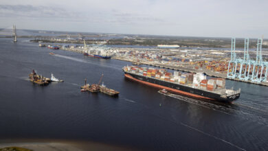 A photograph of a container vessel passing through a shipping channel. There are two smaller boats next to the vessel.