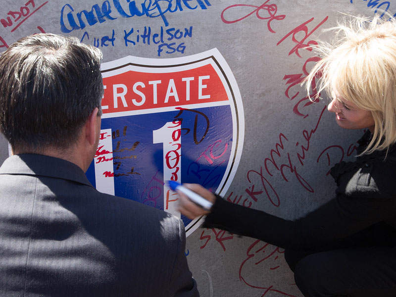 Signing a commemorative sign at a ceremony for I-11. (Photo: Road Traffic Technology)