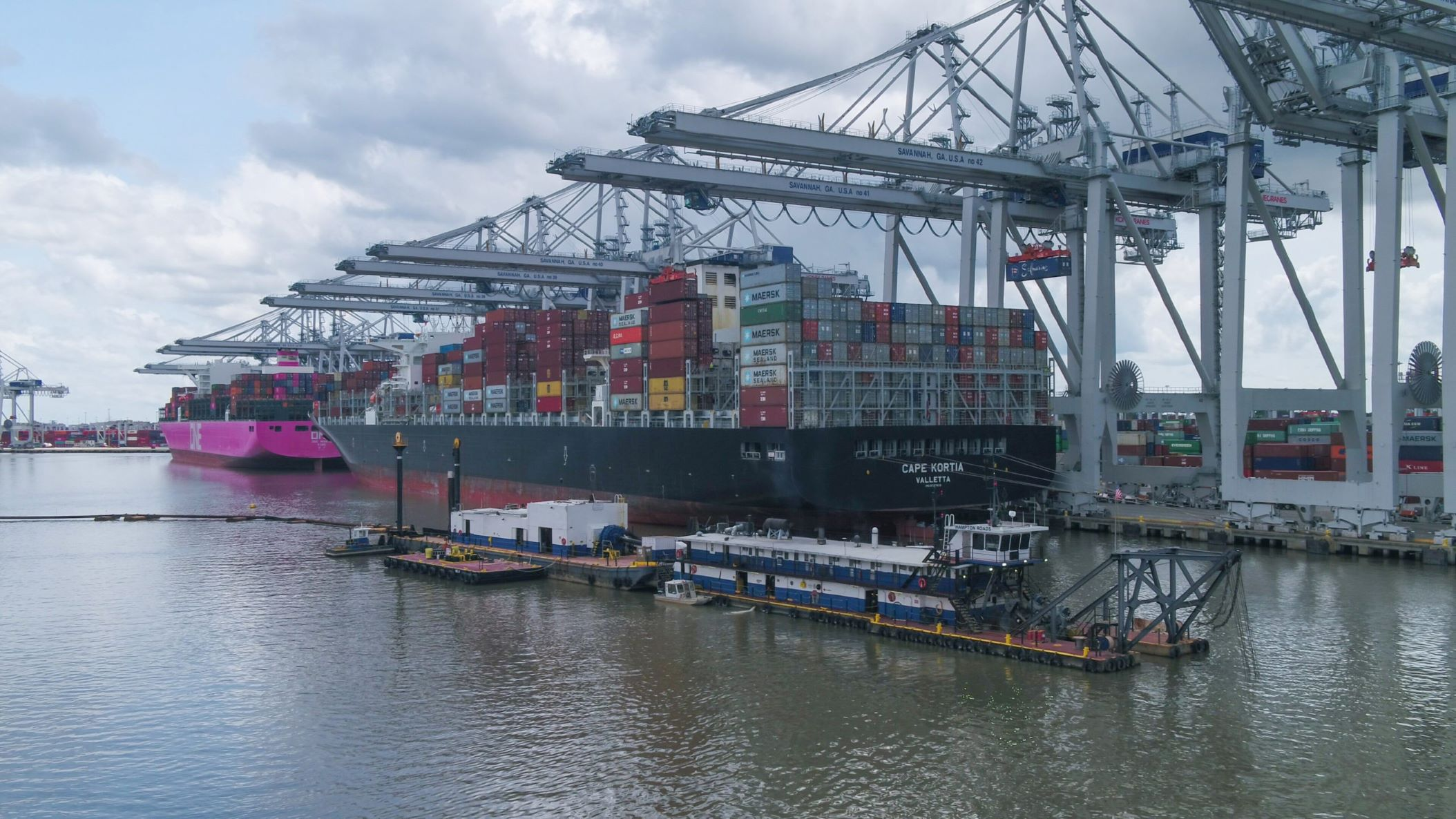 Dredging vessels alongside a massive container vessel docked at a port with large cranes overhead.