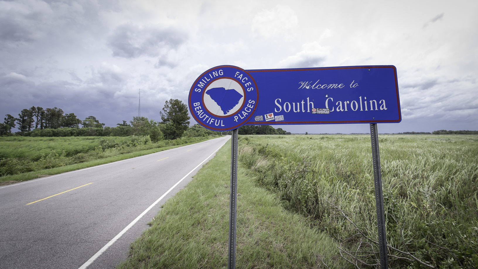 A photograph of a byway sign in the countryside. The sign is next to a road and the sign says Welcome to South Carolina.