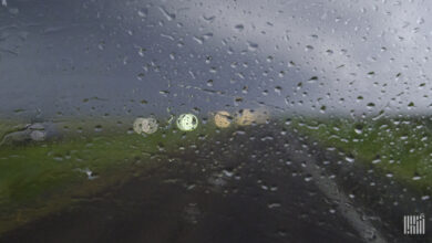Heavy rain on windshield, looking out toward a highway.