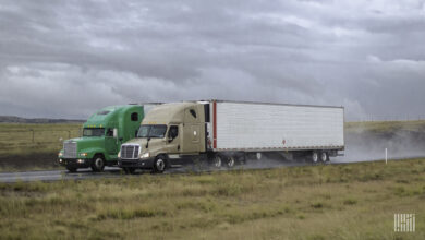Side-by-side tractor-trailers heading down a highway in the rain.