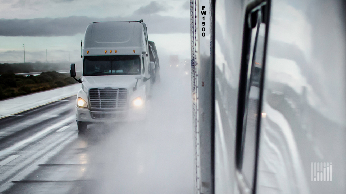 Tractor-trailers heading down a highway in the rain.