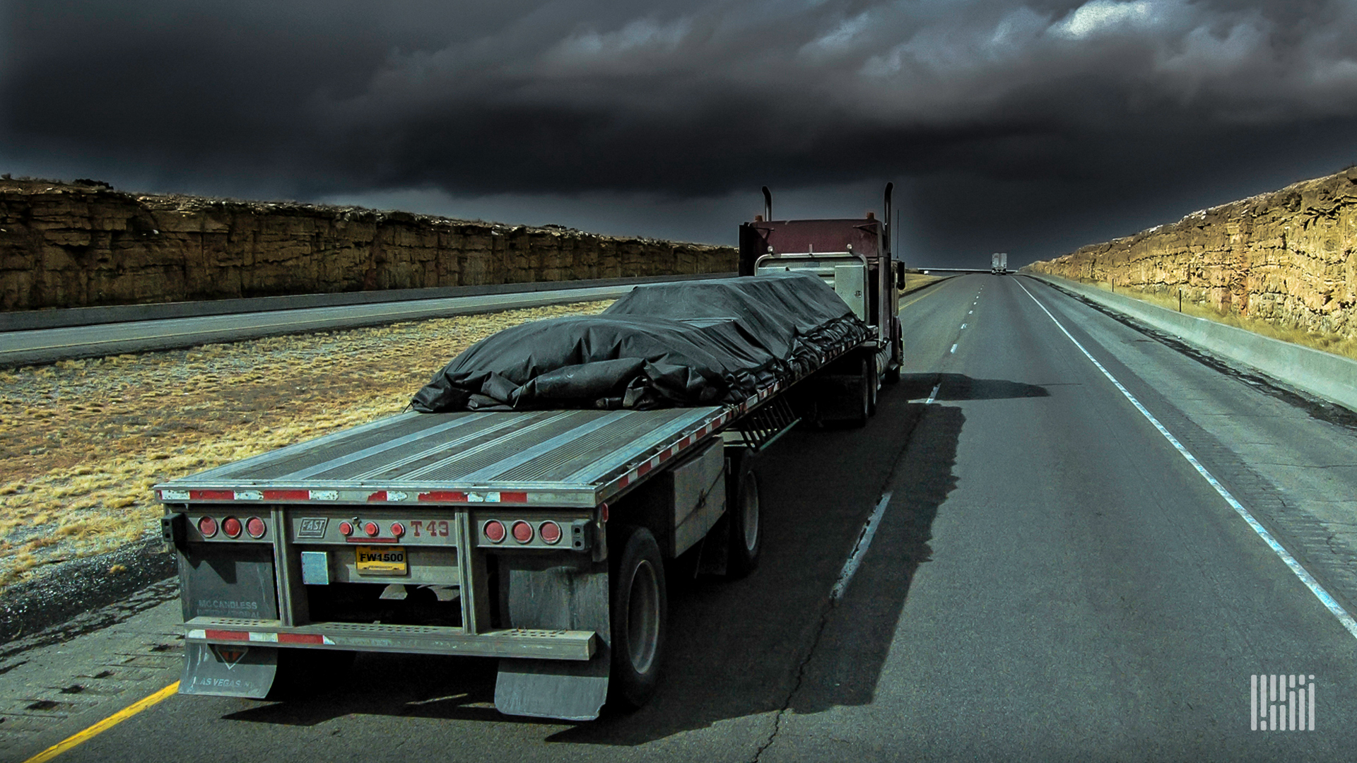 Flatbed tractor-trailer heading down highway with dark thunderstorm cloud across the sky.
