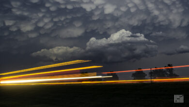 Storm cloud across the sky with vehicle light streaking along the horizon.