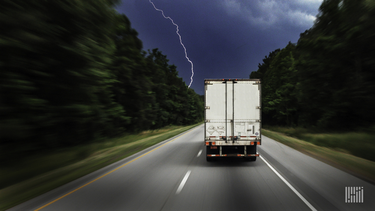 Tractor-trailer heading down a highway with lightning across a dark sky.