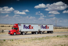 A FedEx truck with a double-trailer moves along a desert highway.